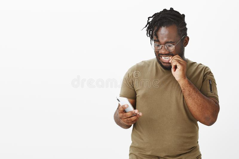 Worried timid attractive dark-skinned guy in olive t-shirt, biting fingernail and staring anxiously at smartphone screen royalty free stock photos