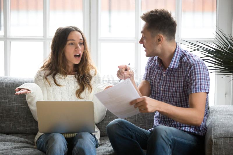 Worried couple arguing about debt bills with laptop and document. Worried unhappy couple arguing about debt or high domestic bills with laptop and documents royalty free stock images