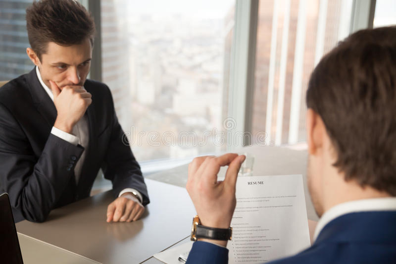 Worried unhired job applicant feeling nervous while employer rev. Worried unhired job applicant feeling nervous while employer or recruiter reviewing bad resume stock photo