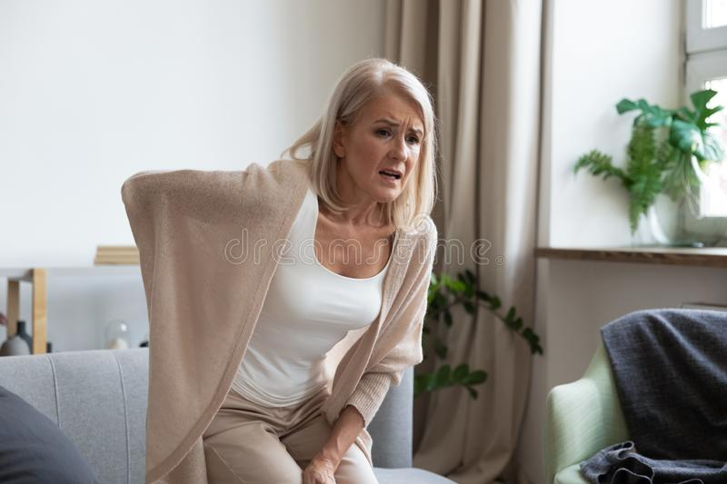 Worried upset mature woman feel hurt sudden back ache. Worried upset middle aged mature woman feel hurt sudden back ache touch sore spine at home alone, tired royalty free stock photo