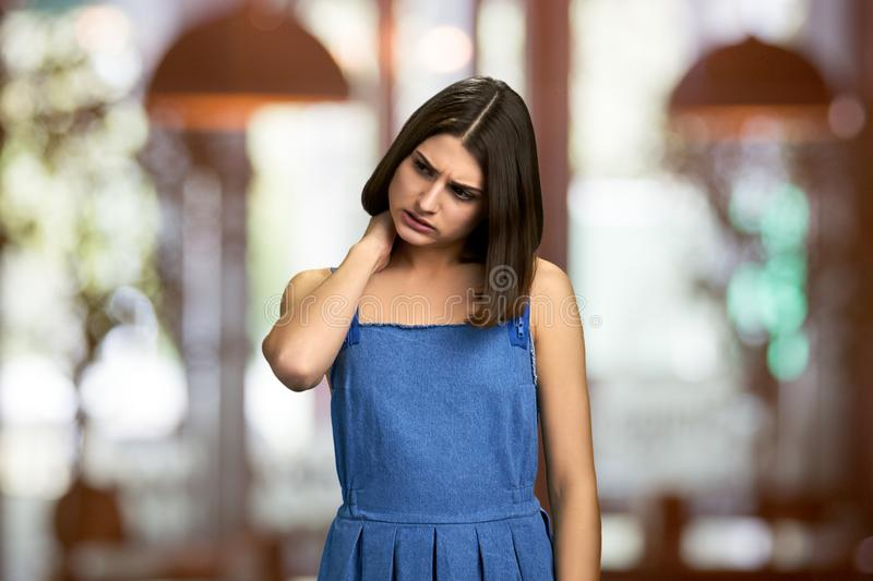 Worried upset woman touching her nape. stock images