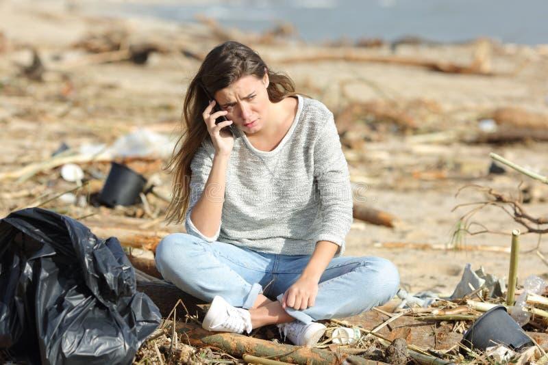 Worried volunteer cleaning a beach calling on phone. Worried volunteer cleaning a dirty beach calling on phone  sitting on the sand stock photos