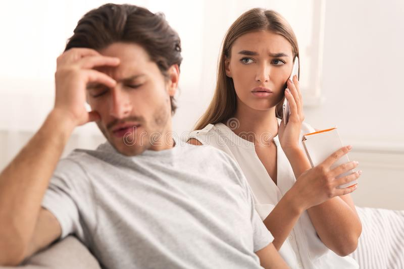 Worried Wife Calling Doctor While Husband Feeling Bad At Home stock images