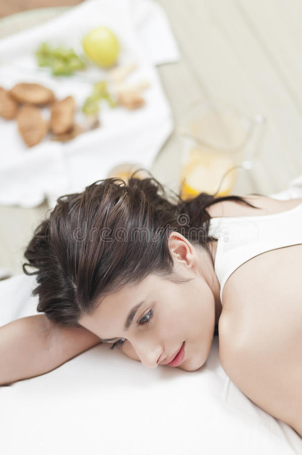 Worried woman on bed with food in the back royalty free stock photos