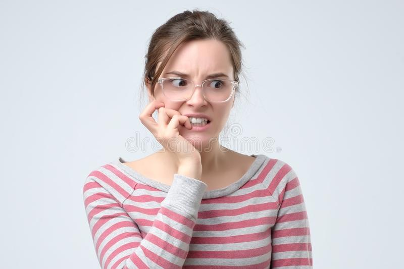 Worried woman bites her fingers and looking aside royalty free stock image