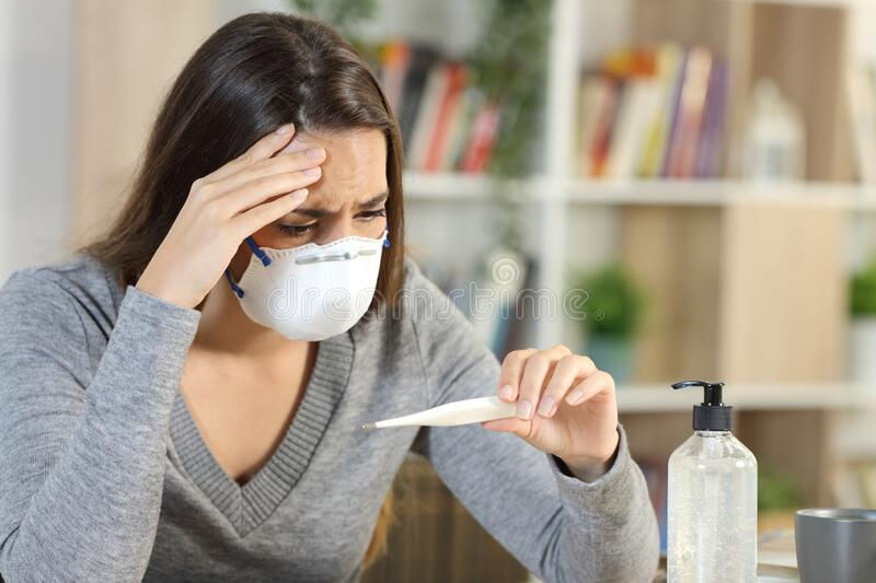 Worried woman with covid-19 fever symptoms at home. Worried woman wearing protective mask with covid-19 fever symptoms looking at thermometer sitting on a desk stock image