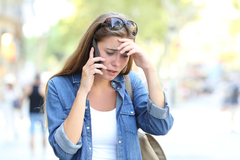 Worried woman having a phone conversation in the street stock photography