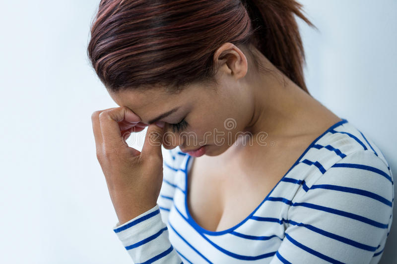 Worried woman with head in hands stock image
