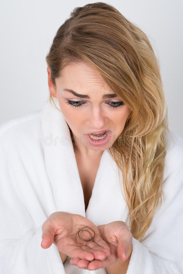Worried woman holding loss hair royalty free stock photos
