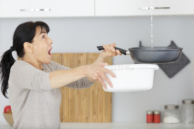 Worried woman with leaking water from ceiling stock photos