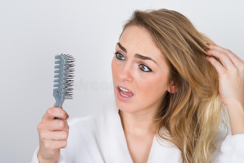 Worried woman looking at comb royalty free stock photos