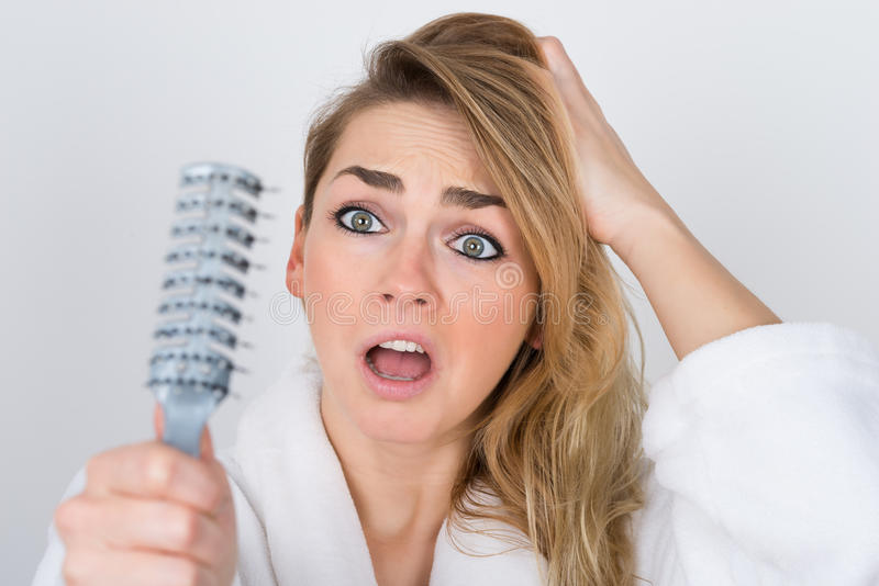 Worried woman looking at comb stock images
