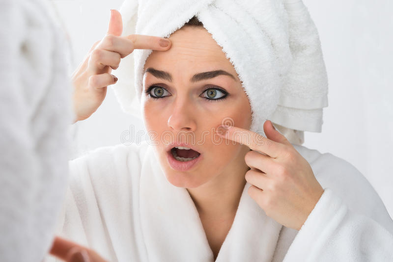 Worried woman looking at pimple on face. Close-up Of Worried Woman Looking At Pimple On Face In Mirror stock images