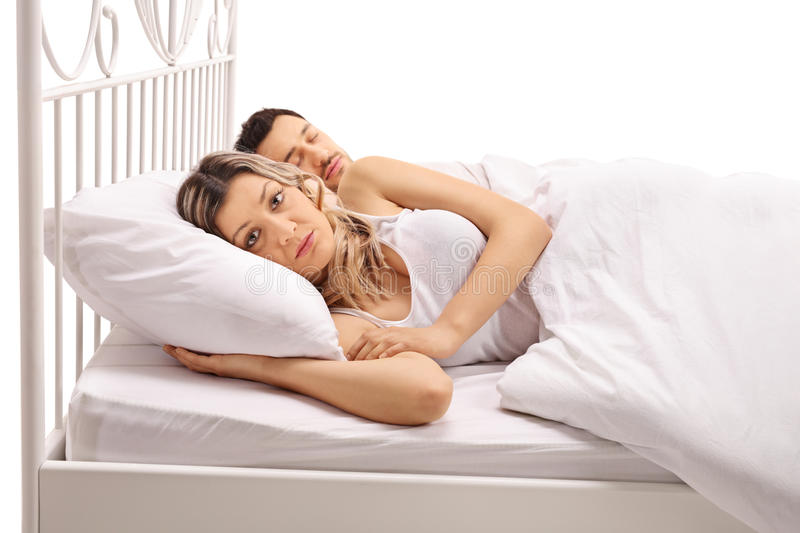 Worried woman lying in bed with a guy stock photography