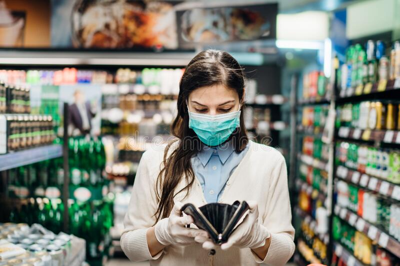 Worried woman with mask groceries shopping in supermarket looking at empty wallet.Not enough money to buy food.Covid-19 quarantine. Lockdown.Financial problems stock photography