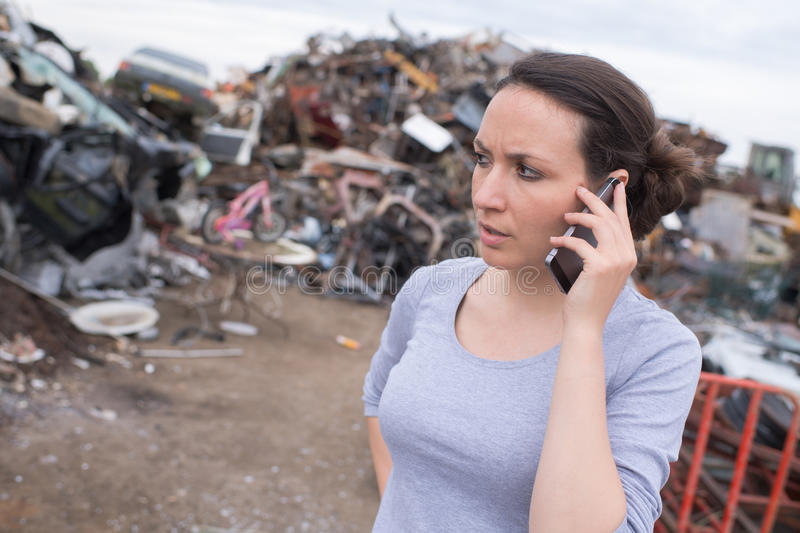 Worried woman on phone at junk-yard stock photo