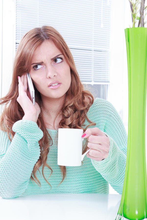 Worried woman receiving bad news over phone. Girl holding cup of coffee and mobile phone with negative reaction stock photos