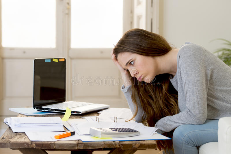 Worried woman suffering stress doing domestic accounting paperwork bills and invoices. Young attractive and desperate woman suffering stress doing domestic royalty free stock photography