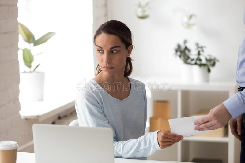 Worried woman taking envelope with bribe from person at workplac. Worried women taking envelope with bribe, money from person at workplace, colleagues, business stock images