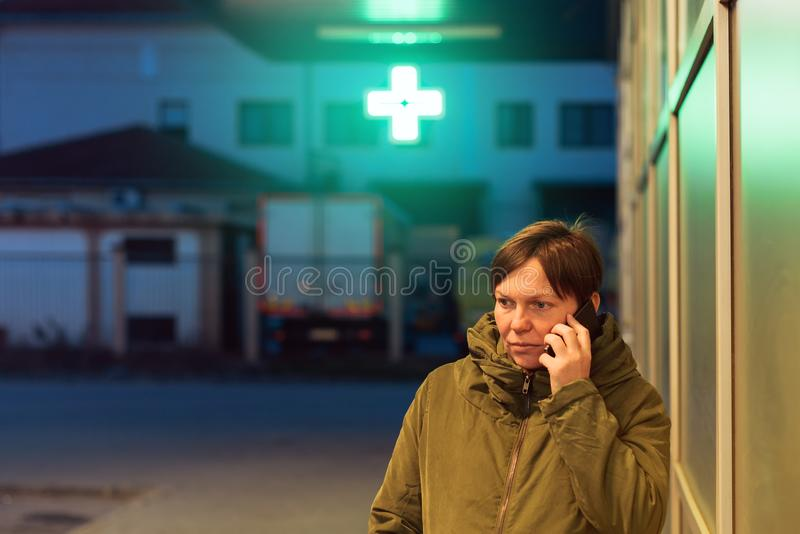 Worried woman talking on mobile phone in front of drugstore royalty free stock photography