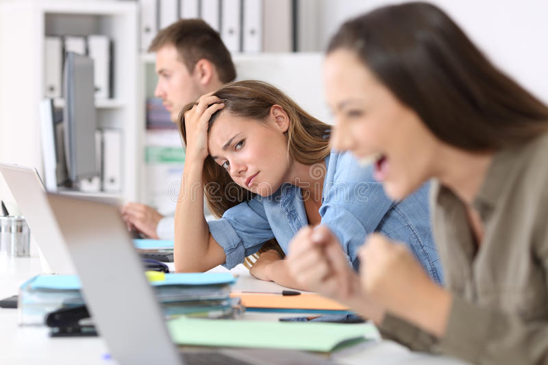 Worried worker beside successful one. Worried worker beside a successful one who is excited reading good news on line at office royalty free stock image