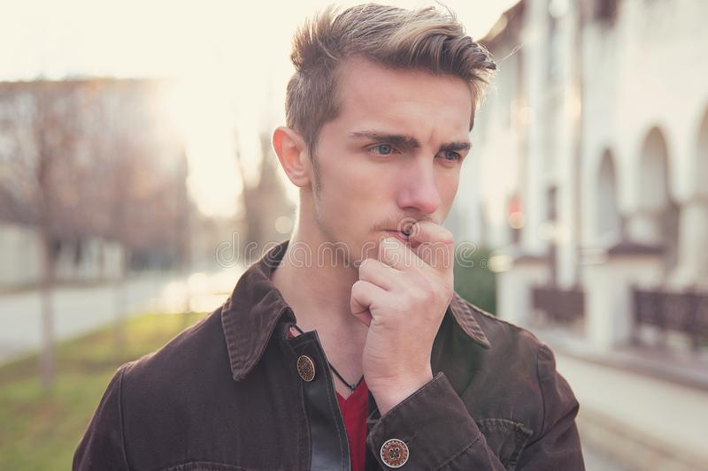 Worried young man biting nails stock photo