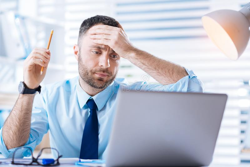 Worried young specialist feeling upset while noticing a mistake in his work. Mistake. Emotional smart young specialist touching his forehead and looking at the stock photography