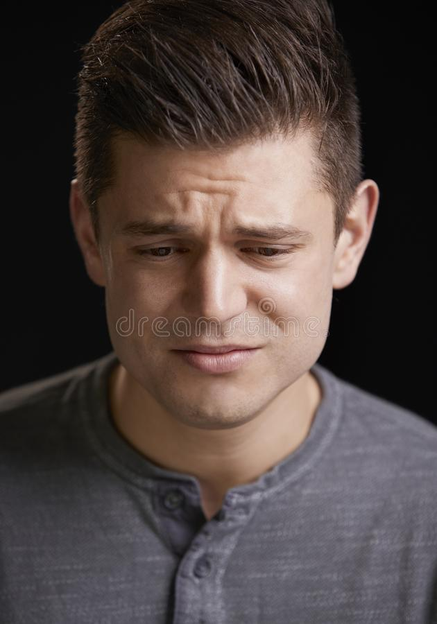 Worried young white man looking down, vertical portrait royalty free stock photos