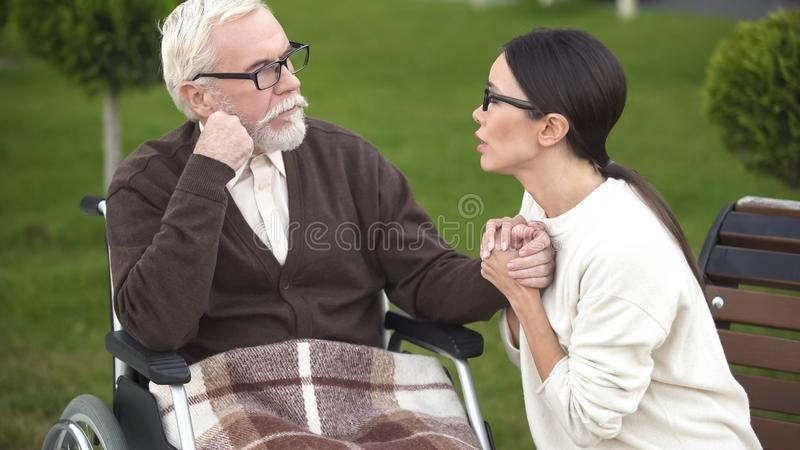 Worried young woman comforting sick grandfather sitting in wheelchair, hospital stock photos