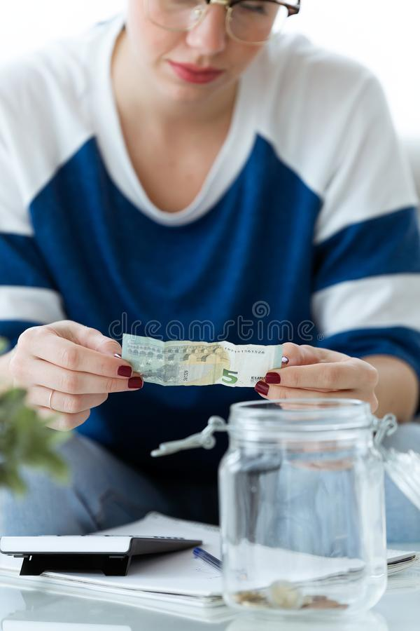 Worried young woman looking her savings while sitting on sofa at home. Shot of worried young woman looking her savings while sitting on sofa at home royalty free stock images