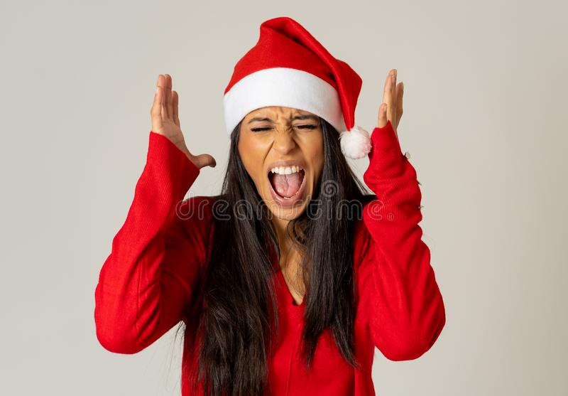 Worried young woman in santa clause hat screaming in stress running out of time for christmas royalty free stock image