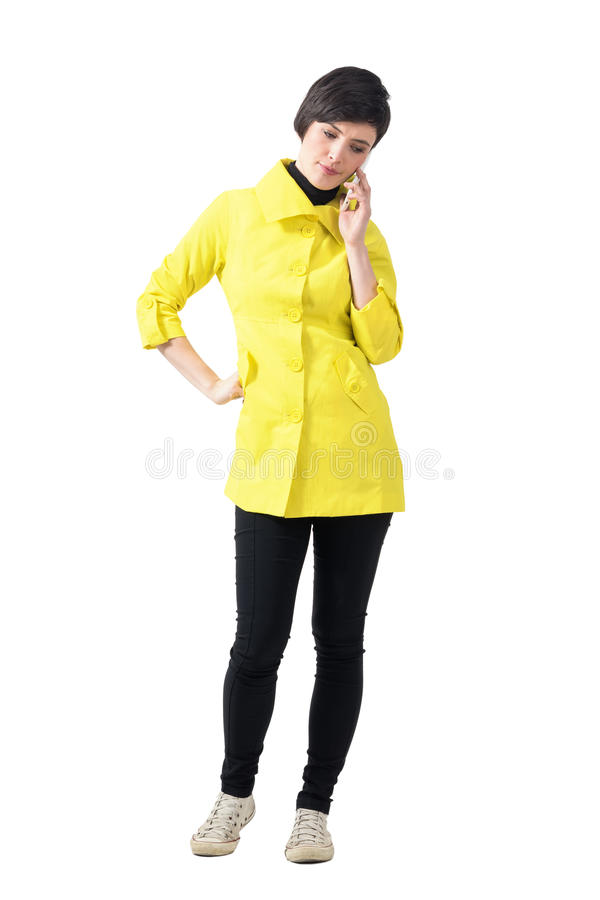 Worried young woman in yellow coat talking on the phone looking down. royalty free stock images