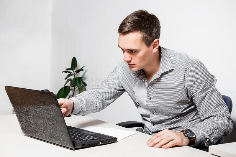Worry businessman using laptop while sitting in office. Indicates a pen on the screen, reads important documents royalty free stock photo