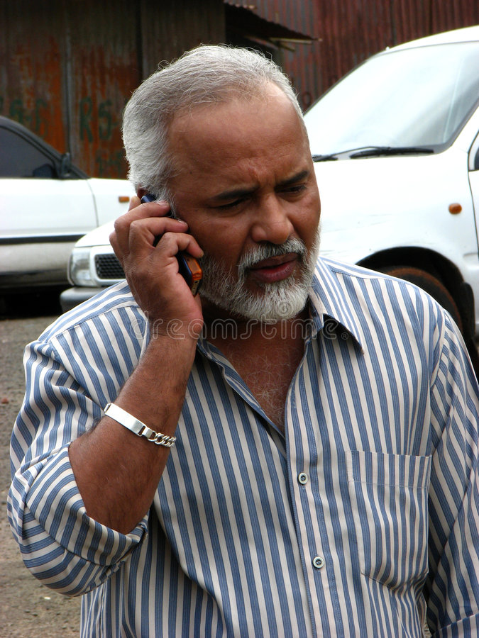 Worrying Communication. A handsome looking Indian senior businessman worried while talking with someone on the phone royalty free stock image