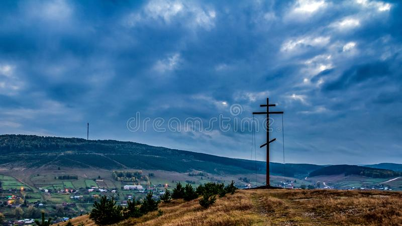 Worship cross standing on the mountain against the background of the regional center of the Upper Avzian After sunset. Against the background of the Ural stock photos