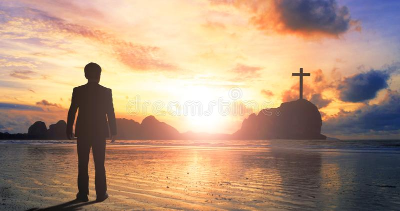 Worship and praise concept: businessman standing by the sea at sunset stock photo