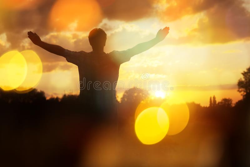 Worship and praise. Silhouette of a man with hands raised in the sunset concept for religion, worship, prayer and praise royalty free stock photography