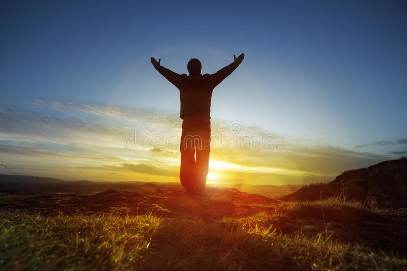 Worship and praise. Silhouette of a man with hands raised in the sunset concept for religion, worship, prayer and praise