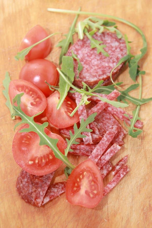 Worst en tomaten op een scherpe raad. royalty-vrije stock fotografie