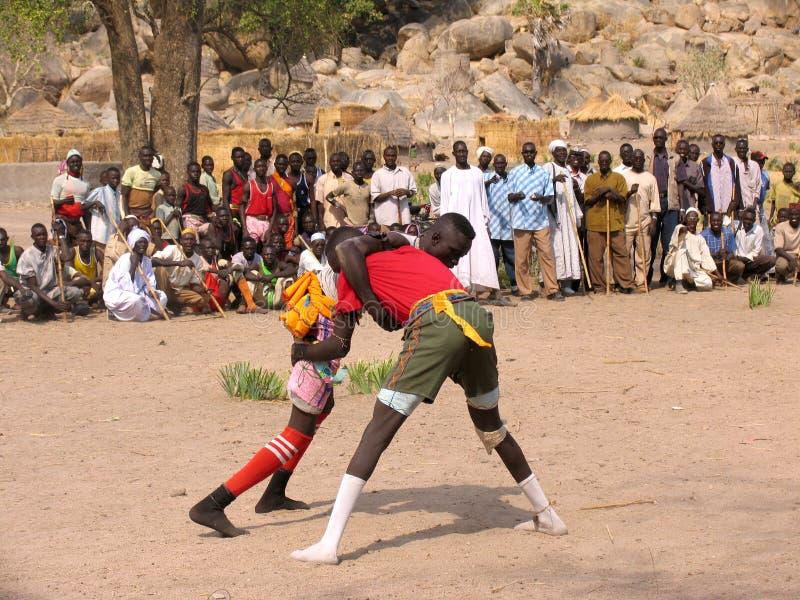 Worstelaars in Nuba-dorp, Afrika stock afbeelding