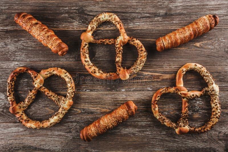 Worsten in bladerdeeg worden verpakt dat Worsten in een deeg en pretzels met zaden op een houten achtergrond stock foto's