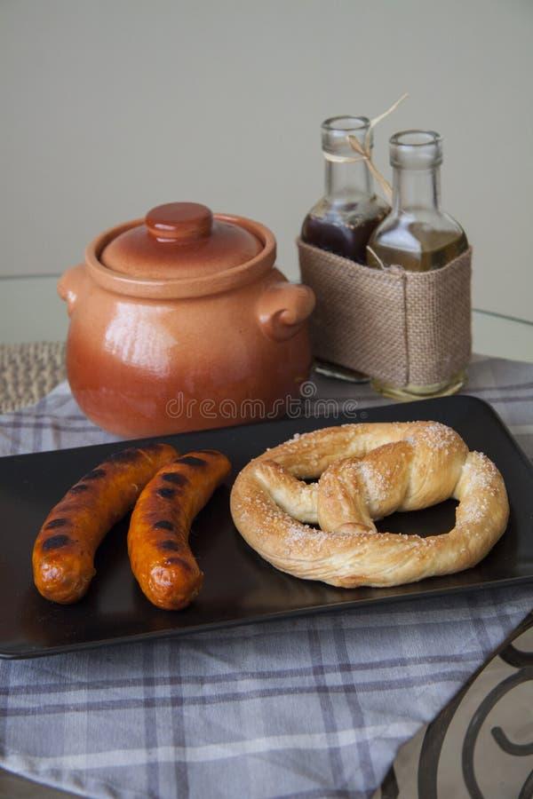 Worsten en brood op zwarte plaat stock foto