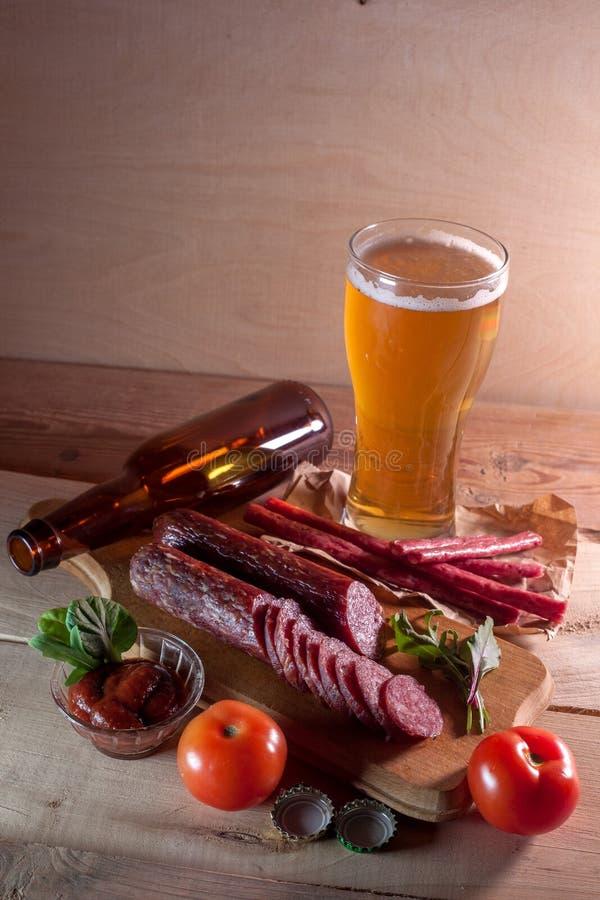 Worsten met glas bier op houten achtergrond stock foto