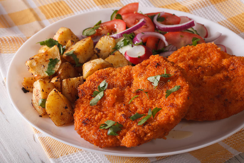 Worstjeschnitzel, gebraden aardappels en plantaardige saladeclose-up Ho stock foto