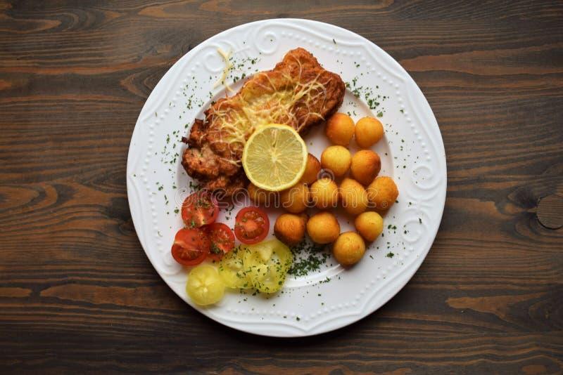 Worstjeschnitzel met aardappelcroquetten en fris gewordene citroen stock afbeeldingen