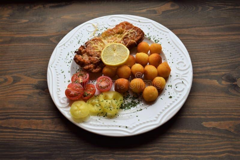 Worstjeschnitzel met aardappelcroquetten en fris gewordene citroen stock fotografie