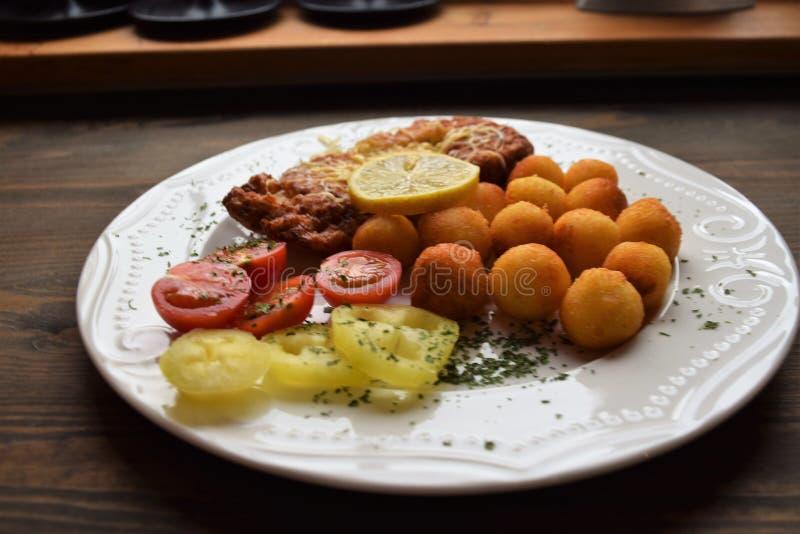 Worstjeschnitzel met aardappelcroquetten en fris gewordene citroen royalty-vrije stock foto