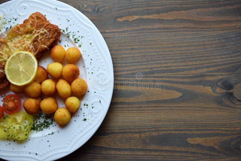 Worstjeschnitzel met aardappelcroquetten en fris gewordene citroen stock foto's