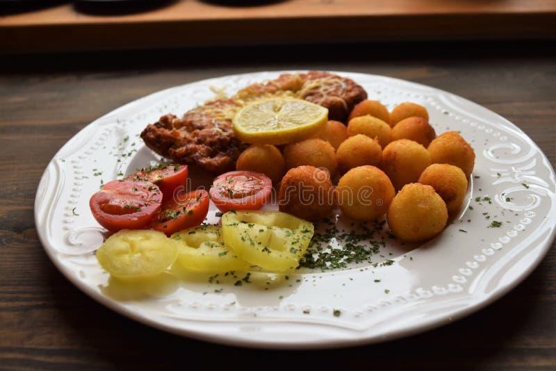 Worstjeschnitzel met aardappelcroquetten en fris gewordene citroen stock foto