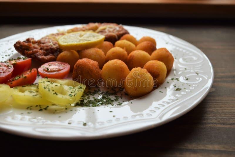 Worstjeschnitzel met aardappelcroquetten en fris gewordene citroen royalty-vrije stock afbeelding